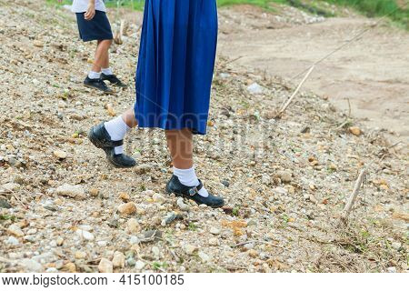 Children Are Walking On The Gravel In The Park.