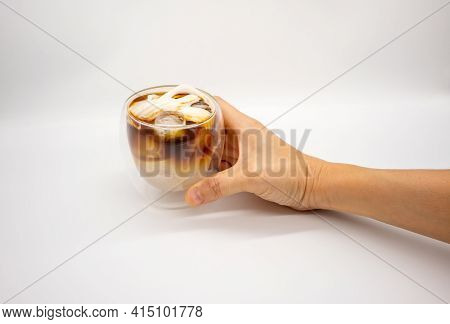 Hand Holding Iced Coconut Coffee In Double Walls Glass Isolated On White Background. Selective Focus