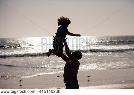 Father Throws Son Up Against The Blue Sky. Dad Throwing Child, Silhouette On Sunset. Men Generation