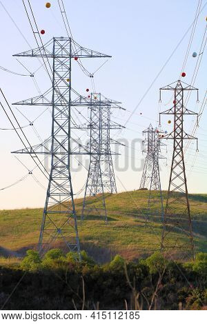 Electric Pylons Holding Electrical Wires Which Came From A Power Source And Being Transported To The