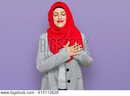 Beautiful hispanic woman wearing traditional islamic hijab scarf smiling with hands on chest with closed eyes and grateful gesture on face. health concept.