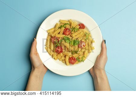 Pasta Food On A Blue Background With Female Hands. Italian Fusilli Pasta With Tomatoes And Basil On