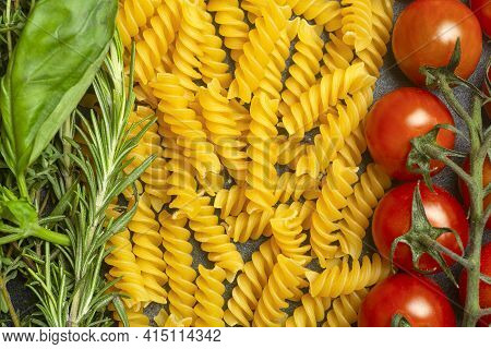 Raw Fusilli Pasta With Tomatoes, Herbs And Basil. Italian Pasta With Ingredients In The Colors Of Th