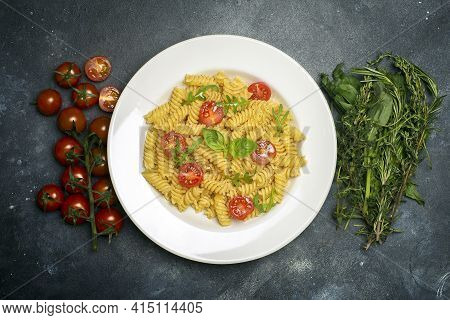 Food Pasta On A Dark Background. Italian Fusilli Pasta With Tomatoes, Herbs And Basil On A White Pla