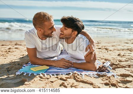 Young gay couple smiling happy lying on the sand at the beach.