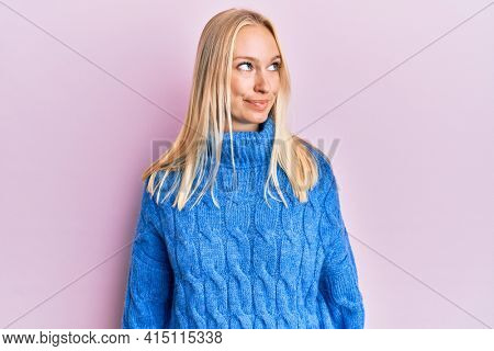 Young blonde girl wearing wool winter sweater smiling looking to the side and staring away thinking.
