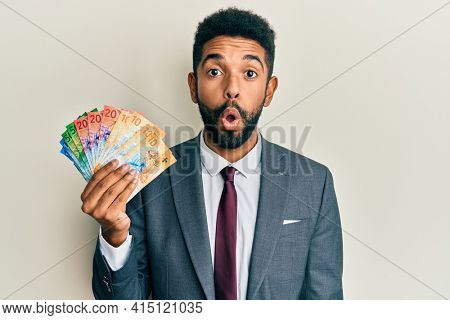 Handsome hispanic business man with beard holding swiss franc banknotes scared and amazed with open mouth for surprise, disbelief face