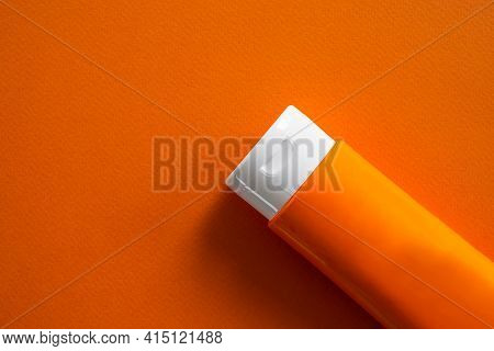 Sun Block Or Sun Screen Tube On Orange Paper.cream Or Lotion Cosmetics For Woman On A Day In The Str