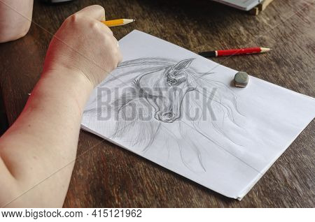 A Middle-aged Woman Draws With A Pencil On White Paper. An Adult Woman Sits At A Wooden Table And Dr