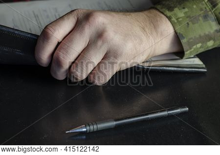 The Hand Of A Mature Man In Military Uniform Is Holding A File Folder On A Black Table. A Middle-age
