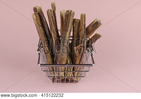 Shopping Basket With Dog Treats On A Pink Background. Chewy Treats In A Metal Basket. Dried Bull Pen