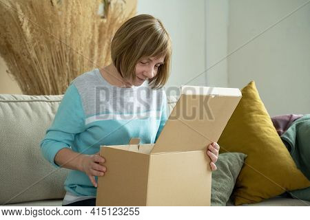 Middle Aged Woman Unpacking Cardboard Box, Sitting On Sofa At Home. Senior Woman Hold Open Cardboard