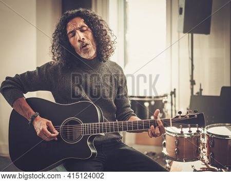 Musician Play Guitar and Sing at Studio . Curly Male Emotionally Perform His New Song.