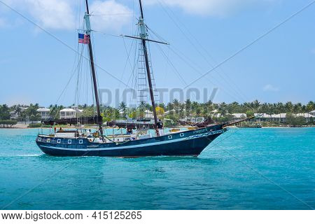 Key West, Usa - 04.30.2017:people Sailing On A Wooden Yacht With Sails Down Into Turquoise Waters Of