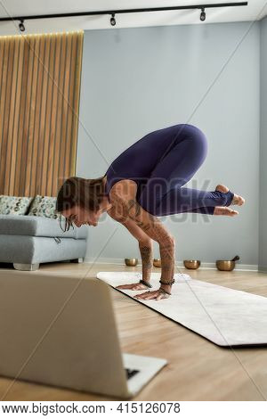 Girl Standing On Her Arms And Training At Home. Young Girl Trainer Standing On Her Arms And Training