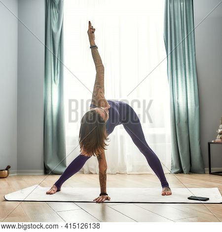 Girl In Sportswear Standing And Performing A Mill Exercise. Young Girl Exercising At Home On Self-is