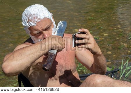Naked Man Chaves Cheek With Huge Knife Holding Blade In Hand Looking At Phone On Natural Background.