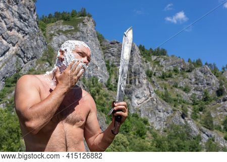 Bald Desperate Man Shaves His Cheek With Long Knife Phone On Natural Background. Morning On Hike