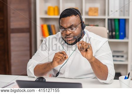 Workplace Of Freelancer. African-american Man Works At Home Office Using Computer, Headset And Other