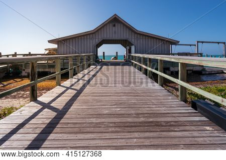 Vintage Building On An Ocean Pier With A Wooden Walk In Front. Sunny Day In Tropical Paradise Of Dry