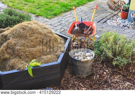Gardening - composter, bucket with stones and wheelbarrow with soil. Bed with mulch and green lawn.