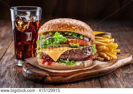 Delicious hamburger with cola and potato fries on a wooden table with a dark brown background behind. Fast food concept.