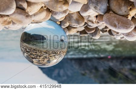 Crystal ball on pebbles near the sea. Original upside down view and rounded perspective of the sky, sea and boat. Original and engaging picture.