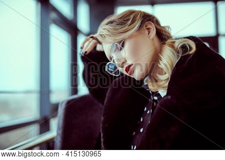 Fashionable young woman in black fur coat, elegant dress and glasses in interiors. Beauty, fashion. Optics and eyewear.