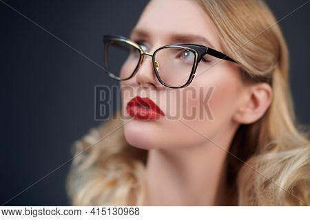 Fashionable blonde woman in elegant glasses looks away. Optics, eyewear. Business style. Close up portrait.