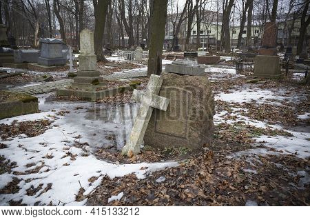 Broken Stone Cross Leaning Against A Gravestone In A Cemetery Covered With Snow And Dry Leaves - Smo
