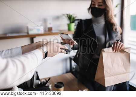 Young Woman In Mask Paying Bill Through Smartphone Using Nfc Technology In A Cafe. Female Customer P
