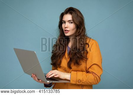 Close-up Portrait Of Beautiful Brunet Curly Young Woman Holding Netbook Computer Looking At Camera W