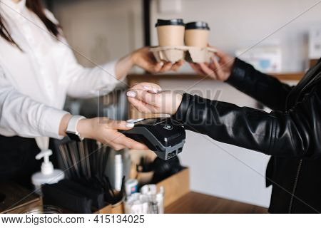 Woman With Face Mask Serving In Coffee Shop Open After Lockdown. Woman Pay Using Smarphone And Nfc T