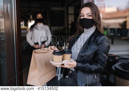 Attractive Female Customer In Face Mask Standing Outdoors By Cafe And Take Away Food And Coffee. Bac