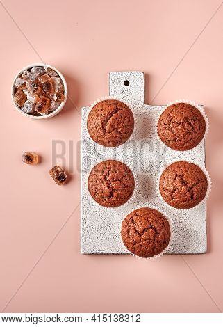 Homemade Chocolate Cupcakes In Baking Paper Forms On Cutting Board On Pink Powdery Background, Verti