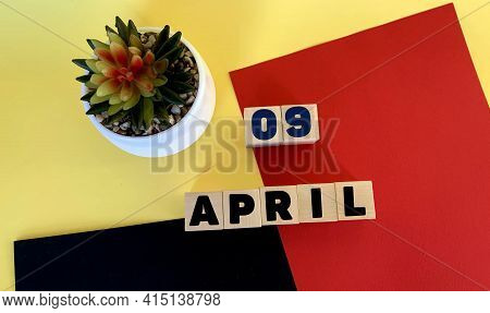 April 9 On Wooden Cubes.next To It Is A Potted Cactus On A Multicolored Red Yellow Black Background.