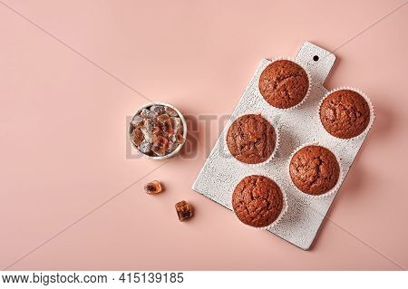 Homemade Chocolate Cupcakes In Baking Paper Forms On Cutting Board On Pink Powdery Background, Top V