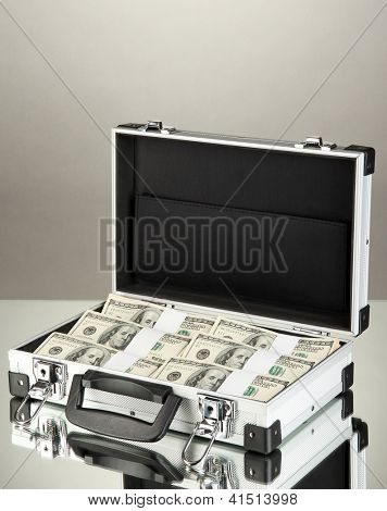 Suitcase with 100 dollar bills on grey background