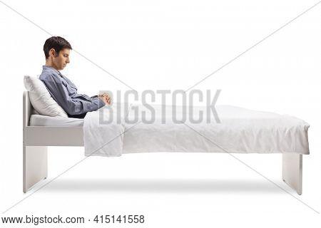 Sleepy man in pajamas sitting on a single bed under duvet isolated on white background