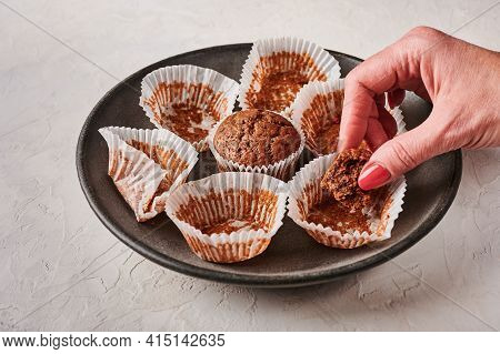 Womans Hand Holds A Piece Of Chocolate Cupcake, Next To Empty Wrappers On Dark Plate On Wooden Backg