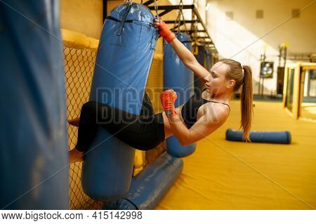 Female MMA fighter in bandages hits the bag in gym
