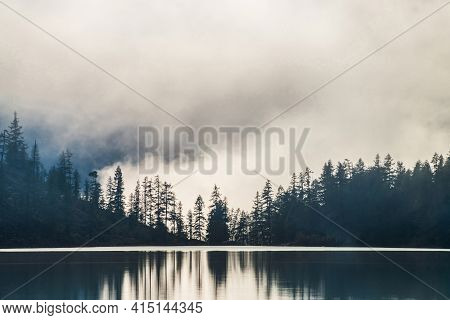 Silhouettes Of Pointy Tree Tops On Hillside Along Mountain Lake In Dense Fog. Reflex Of Pines To Cal