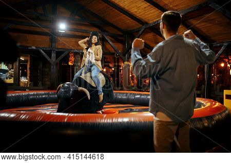 Love couple on rodeo attraction in amusement park