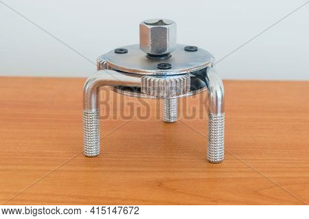 Silver Three Jaw Car Filter Spanner On Wooden Table.