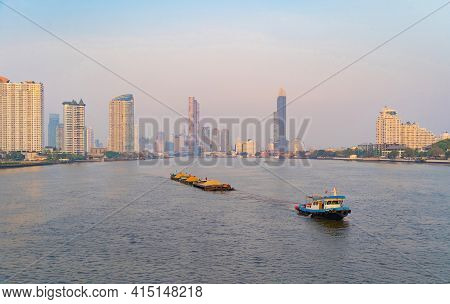 A Boat Ship In Bangkok City Skyline By Chao Phraya River In Thailand. Financial District And Skyscra