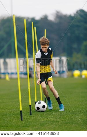 Soccer Training Drill For Youth Junior Player. Young Teenage Boy Running And Dribbling Ball Between