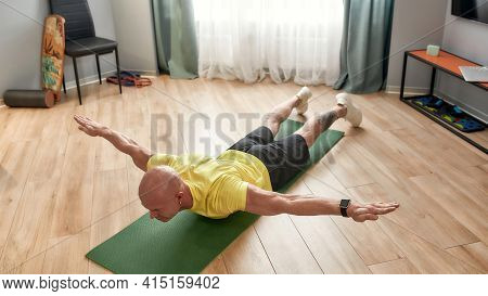 Daily Workout Routine. Mature Man In Sportswear Exercising On Yoga Mat At Home. Sport, Fitness And H