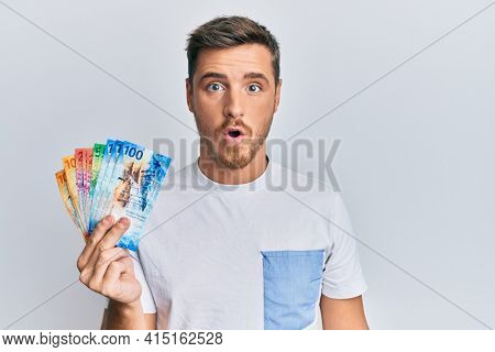 Handsome caucasian man holding swiss franc banknotes scared and amazed with open mouth for surprise, disbelief face