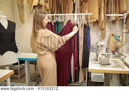 Female Fashion Designer Working On New Womenswear Collection For Clients In Cozy Workshop Studio, Dr