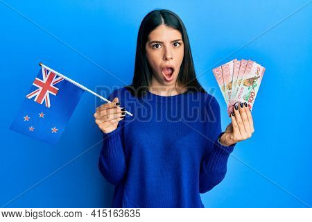 Young hispanic woman holding new zealand flag and dollars in shock face, looking skeptical and sarcastic, surprised with open mouth